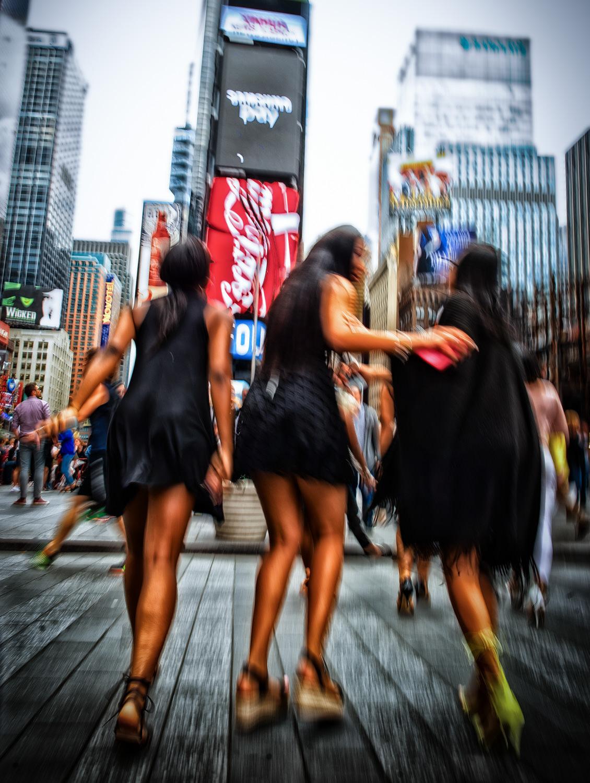 Fest og ballade på Times Square. Billedet er rystet af bevægelse, kvinderne er dullet op til fest, og der er knald på farverne. Essensen af Times Square.