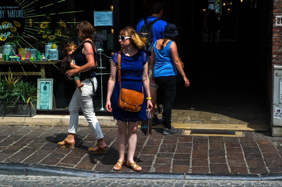 Pigen her er bare en fest. Sandalerne, hendes blege ben, den rødbrune lædertaske, de hvide og STORE solbriller, det gule armbåndsur, håret, der blafrer i vinden og næsten matcher taskens farve. Og så den dybblå kjole. Hun var ikke til at stå for.