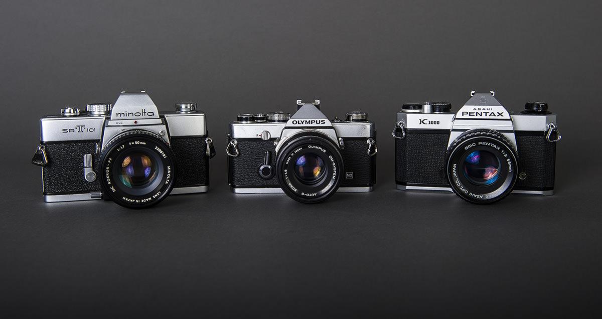 Minolta SRT 101 (1973), Olympus O-M1 (1974), Pentax K1000 (1976). Årstallene er ca.
