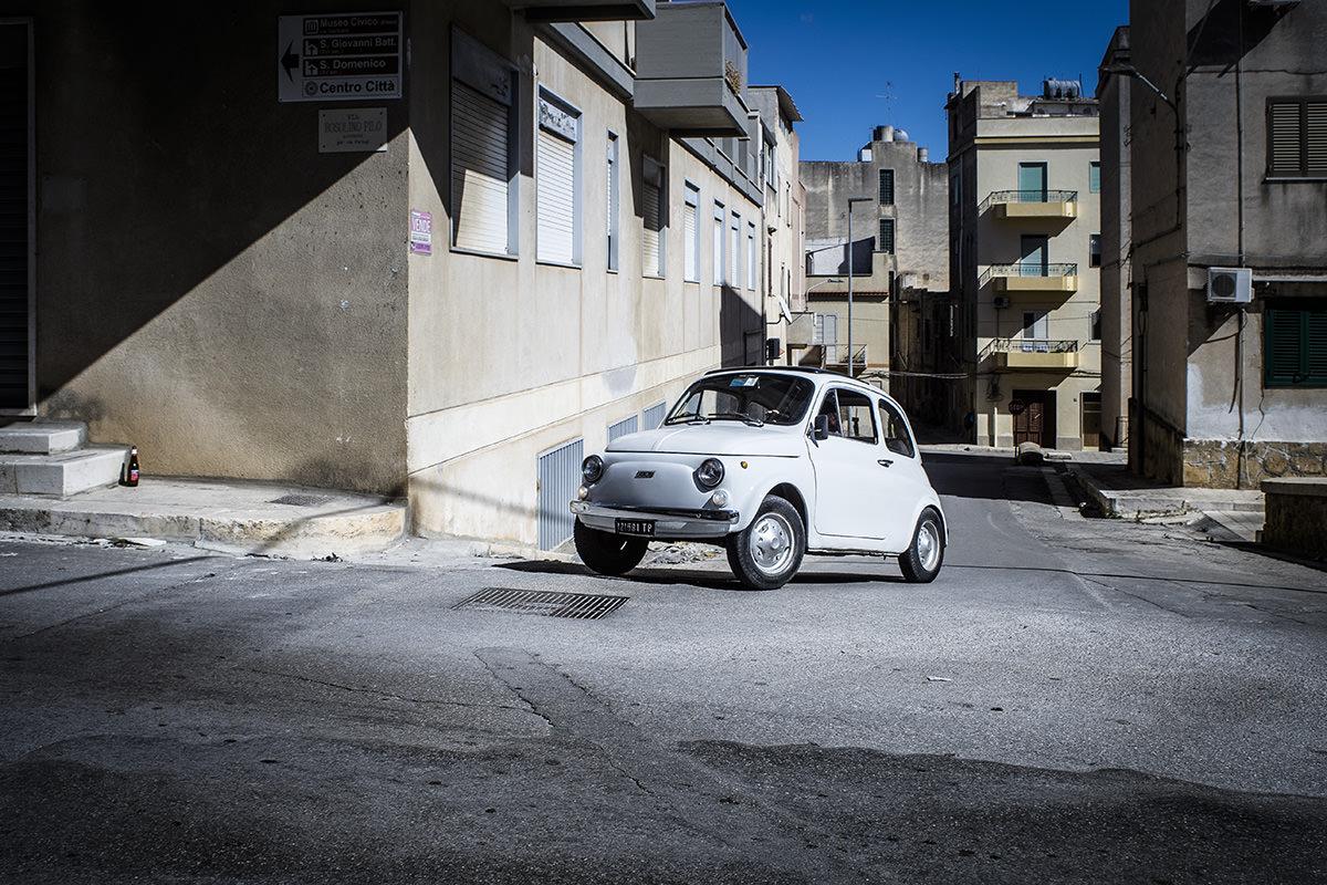 Castelveltrano, Sicilien. Et næsten kubistisk, surrealistisk gadesnapshot. Det er som om, der er noget galt med dimensionerne her. Jeg synes, den lille Fiat 500 virker underdimensioneret i forhold til omgivelserne. Men det er IKKE en modelbil, jeg har sat ind i billedet!